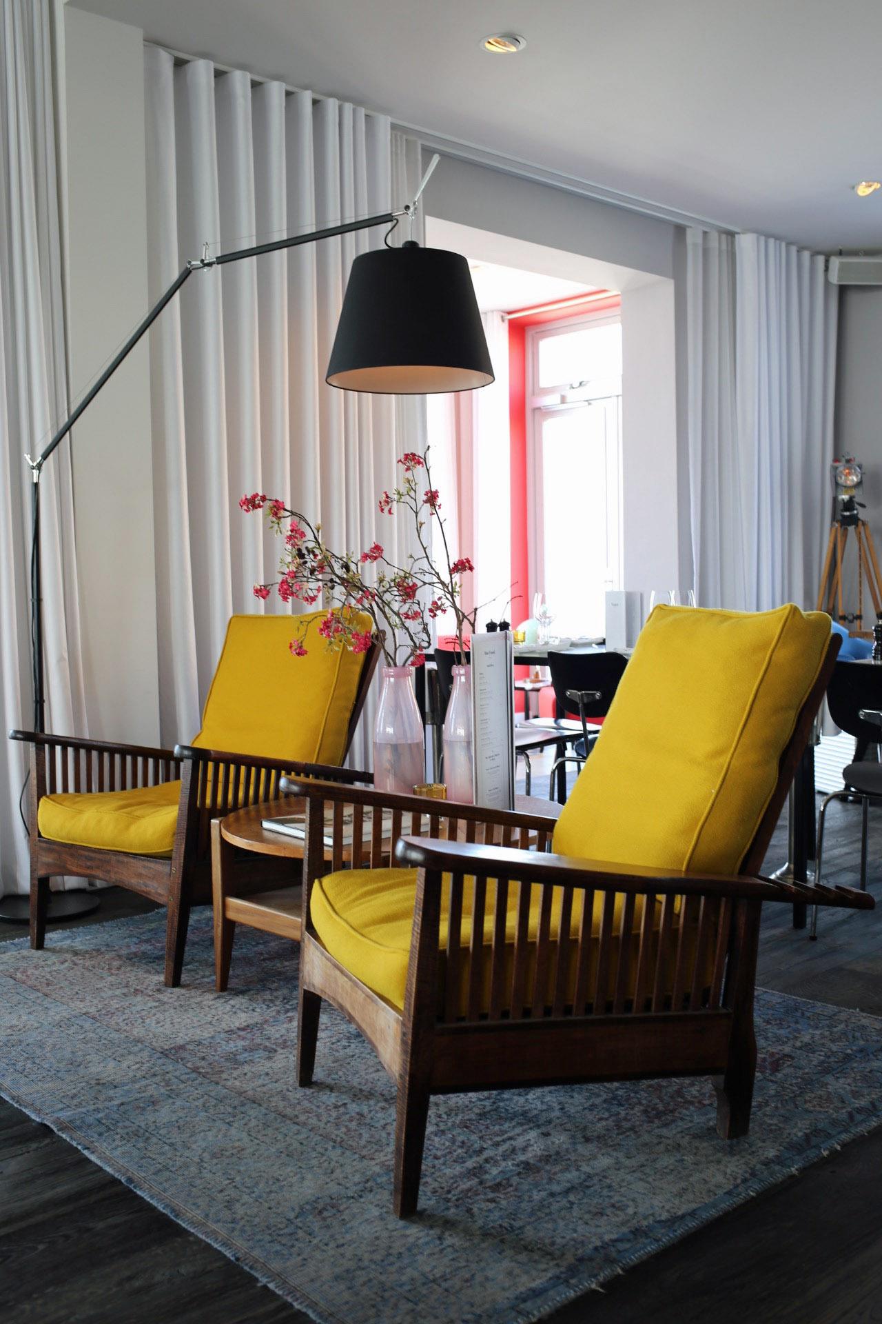 Yellow chairs in the lobby at Vesper Hotel Noordwijk | Design Hunter