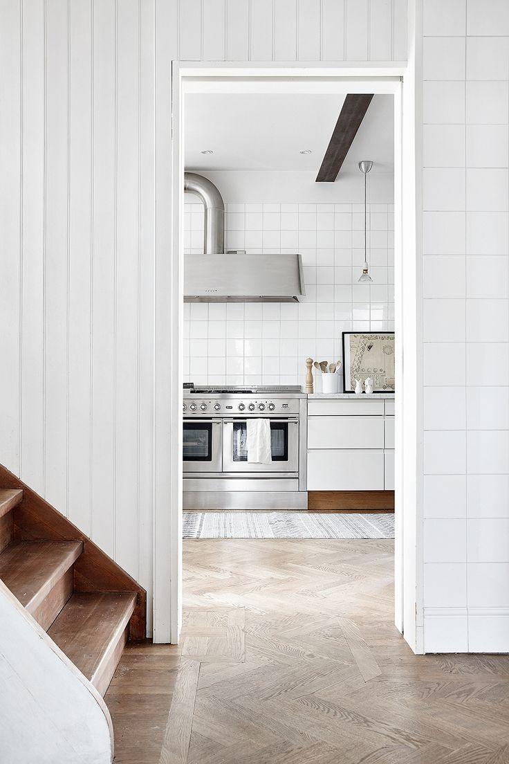 White kitchen with herringbone parquet flooring