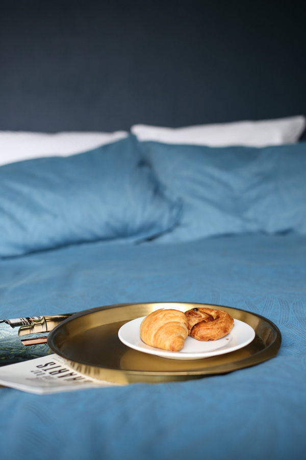 Brass breakfast tray on blue bed | Design Hunter
