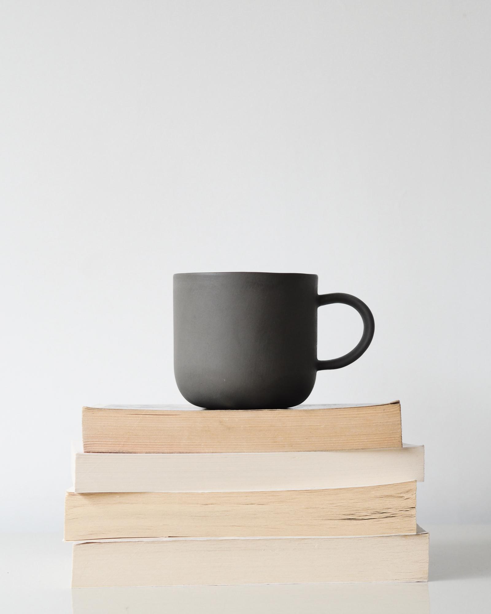 Books and grey mug