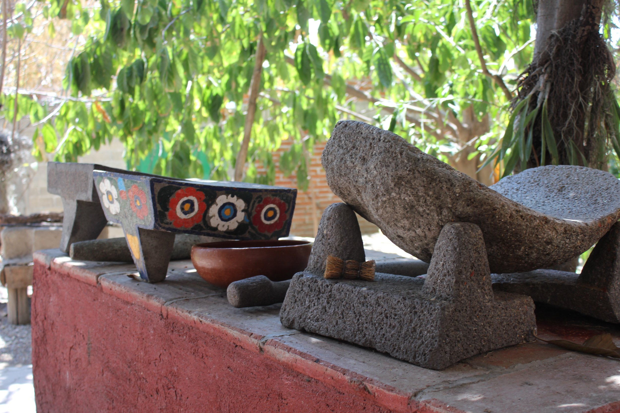 The metate used by Reyna's grandmother sits to the right of a recent version widely available in local markets.