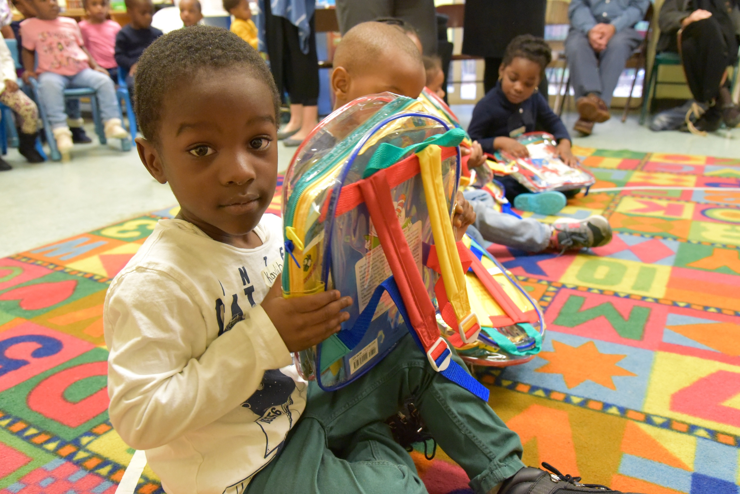Pre-k students receive books from Inner City - Inner Child programs.  Photo by Lana Wong