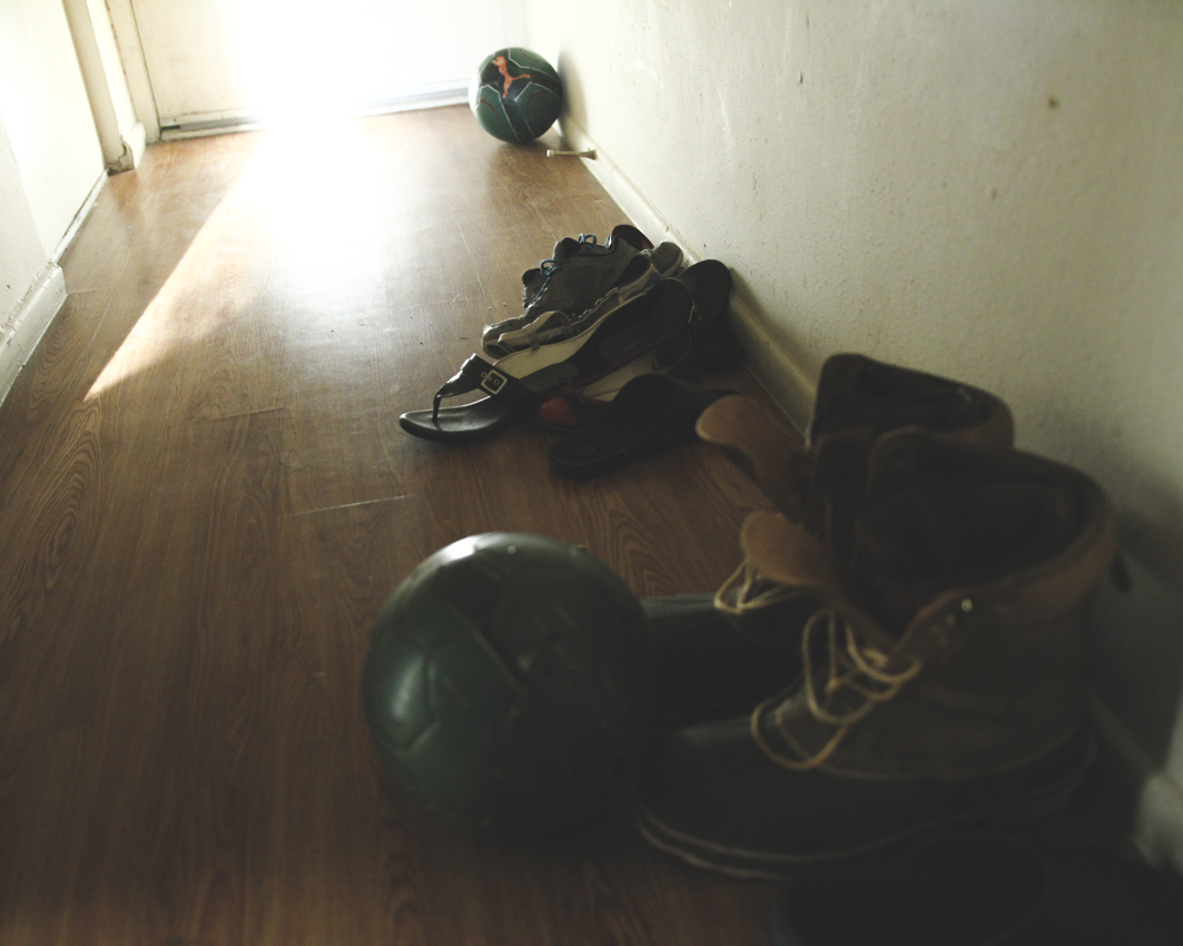 The entrance into the Acharya's apartment is filled with the shoes and soccer balls of visitors. The apartment complex is a hub for refugee families from all over the world- from Somalia to Burma to Iraq. The climate is both tense and communal. Racism and gang activity are both prevalent in the area, but families still try to uphold cultural values, such as keeping the door open to visitors and having friends over for dinner or tea.