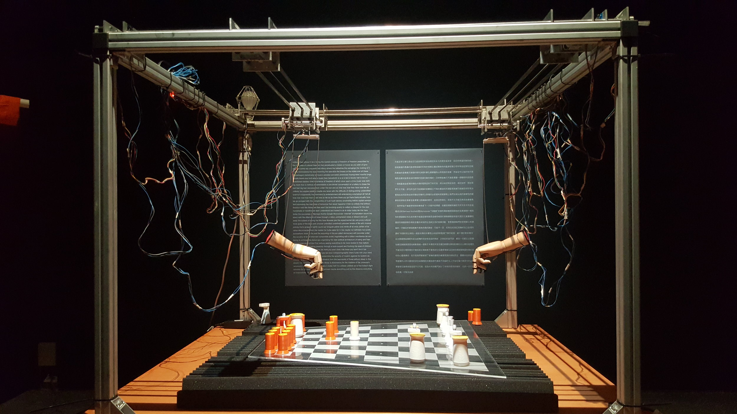 An out of the world, oddly-shaped chess game played between two wooden mannequin hands that are made alive by an explosion of wires dangling behind them.