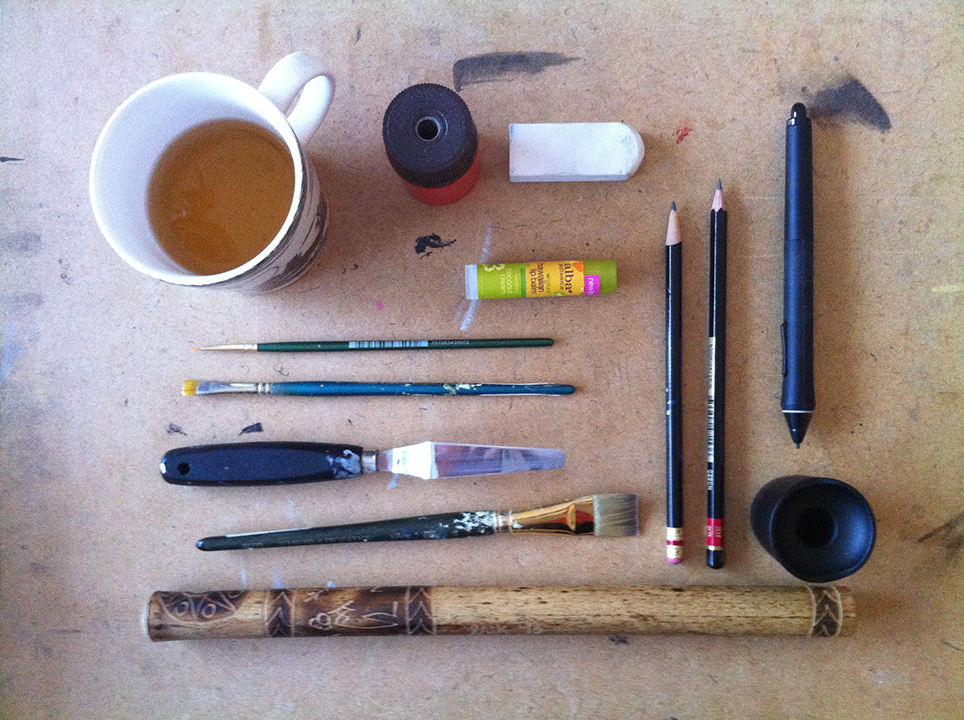 Cup of tea, brushes, pencils, chapstick, wacom tablet pen tool and wooden flute