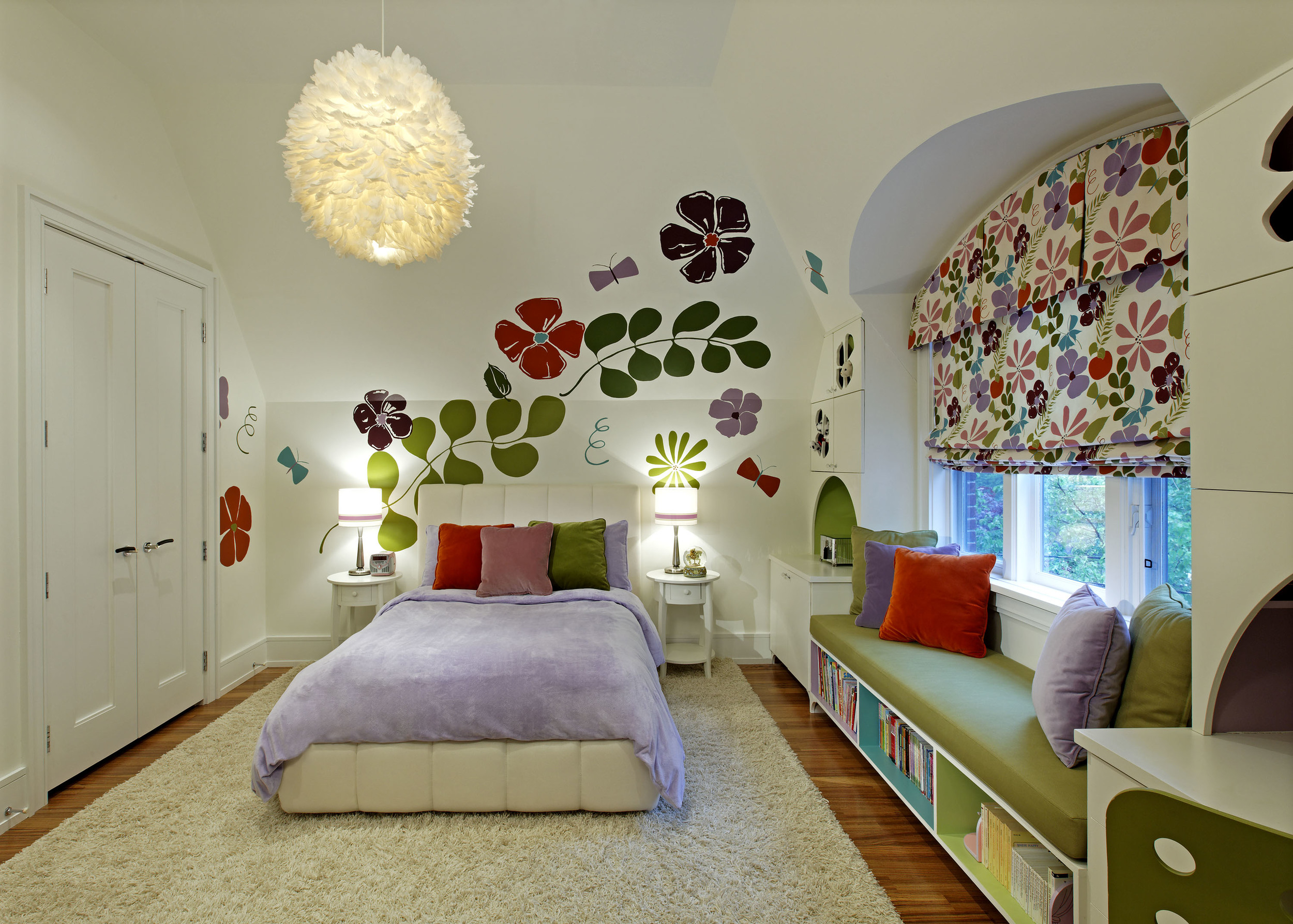Within a traditionally styled house, a clean, open and contemporary interior responds to this young family's modern tastes. This 9 year-old girl's garden room employs bright colour, exuberant graphics, handy storage and an offbeat feathered pendant light fixture that will still appeal when she is 13.