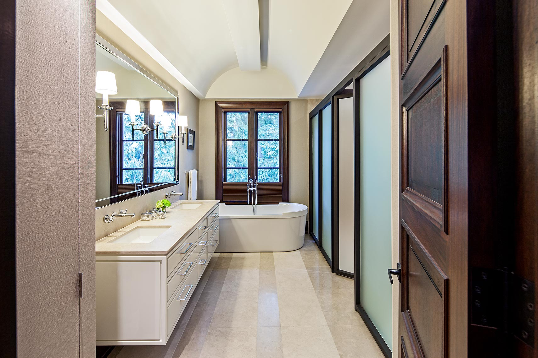 The barrel vaulted ceiling with recessed lighting emphasizes the serene and orderly nature of this peaceful retreat. Bronze-framed frosted glass partitions conceal the shower and toilet room. Top down/bottom up, bronze-toned fabric blinds create privacy while preserving the view of the lush landscape surrounding this river valley home. Grasscloth covering the foreground storage cabinet adds an unexpected textural element.