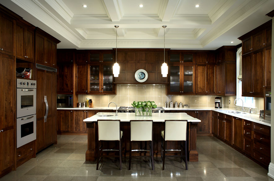 This client wanted his new home to celebrate his North American achievements and European heritage. After conceiving all the interior volumes and spaces, we used a variety of motifs, textures and patterns so that each room has its own mood, yet a common richness unites the home. The generous kitchen's traditional styling in the deeply coffered ceiling and elegantly detailed walnut cabinetry contrasts with gleaming glass tile and stone surfaces and contemporary seating.