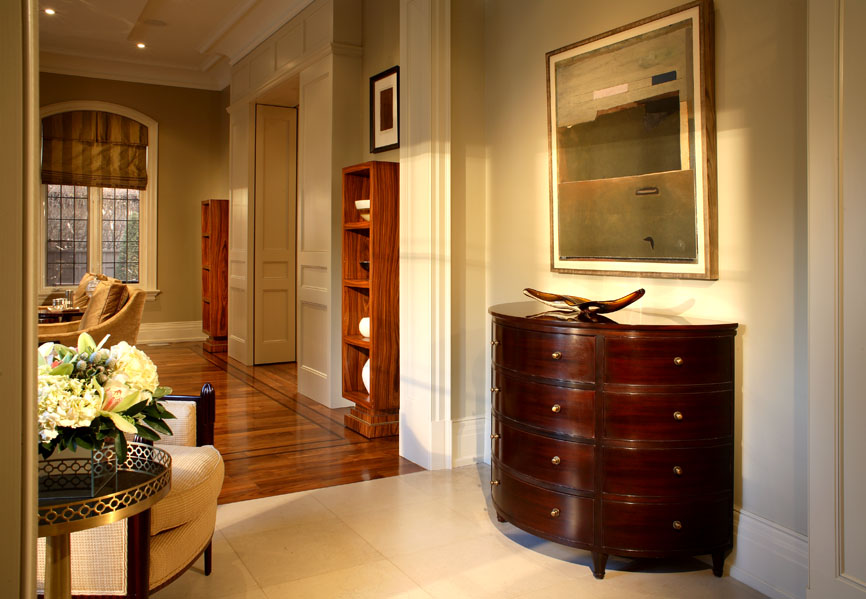 Each room in this client's home has its own mood, achieved with a variety of motifs, textures and patterns. Rich wooden furnishings alternating with art work and palely gleaming millwork details create an appealing rhythm along this passageway.