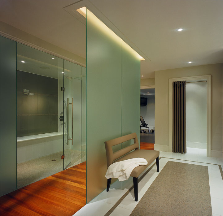 This client wanted his new home to celebrate his North American achievements and European heritage. In his luxury spa, the compressed glass and glass mosaic tile floor glistens as does the dramatically-lit frosted glass divider that demarcates the teak-floored wet area. The wall-to-wall glass partition at left is frosted for privacy at toilet and shower areas and is clear at the steam room where it parallels the frosted glass divider.