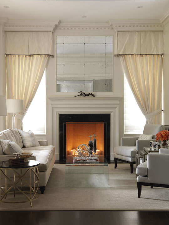 Although they love traditional design, this Florida-based couple wanted their Canadian summer home to be a fresh, light and lively place for the whole family, including very young children and a dog. We gave them the freshness that reflects their lifestyle, while respecting the neoclassical character of the home. This living room combines very simple, contemporary lines with traditional details, such as the drapery and fireplace mirror treatments artfully concealing built-in fire shutters.