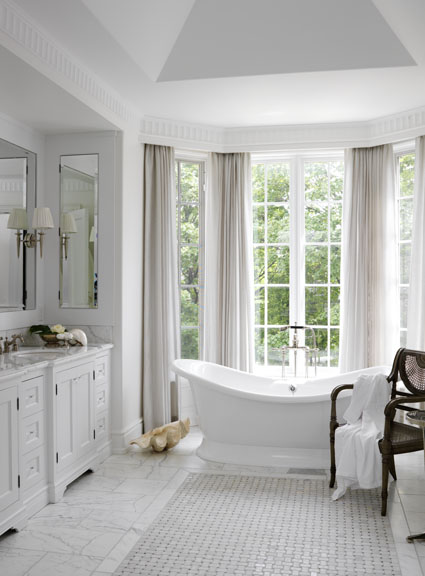 The light-filled Georgian-styled, Canadian summer home we created for this Florida-based couple reflects a lifestyle with very young children, a dog and a busy social calendar. This crisp, white and elegant master bath incorporates very simple built-in cabinetry and lush floor-length drapery within a traditionally detailed space, creating a blissfully serene refuge.
