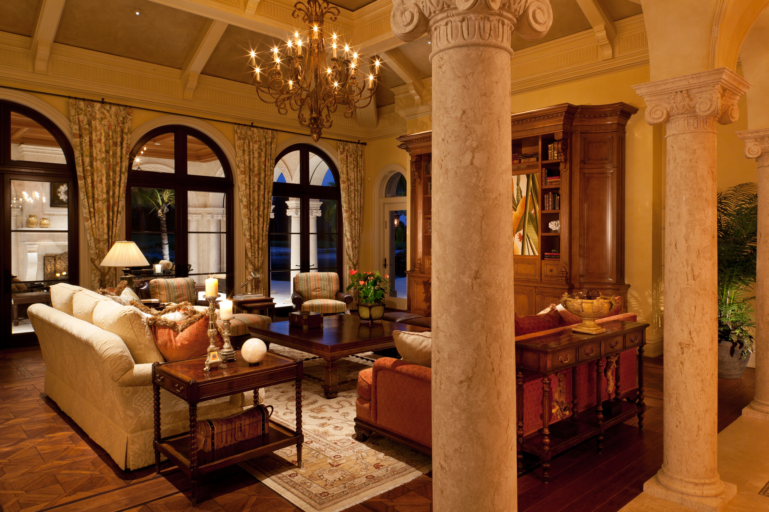 Opening onto the lanai, the family room of this lovely Florida home also connects to dining room across the elegant colonnade of solid carved Syrian stone. The columns and the intricate ceiling structure were all carefully planned and detailed. So, too, was the massive 12 foot tall wall unit, which was executed in select hard white maple finished with multiple glazes that create its warm character.