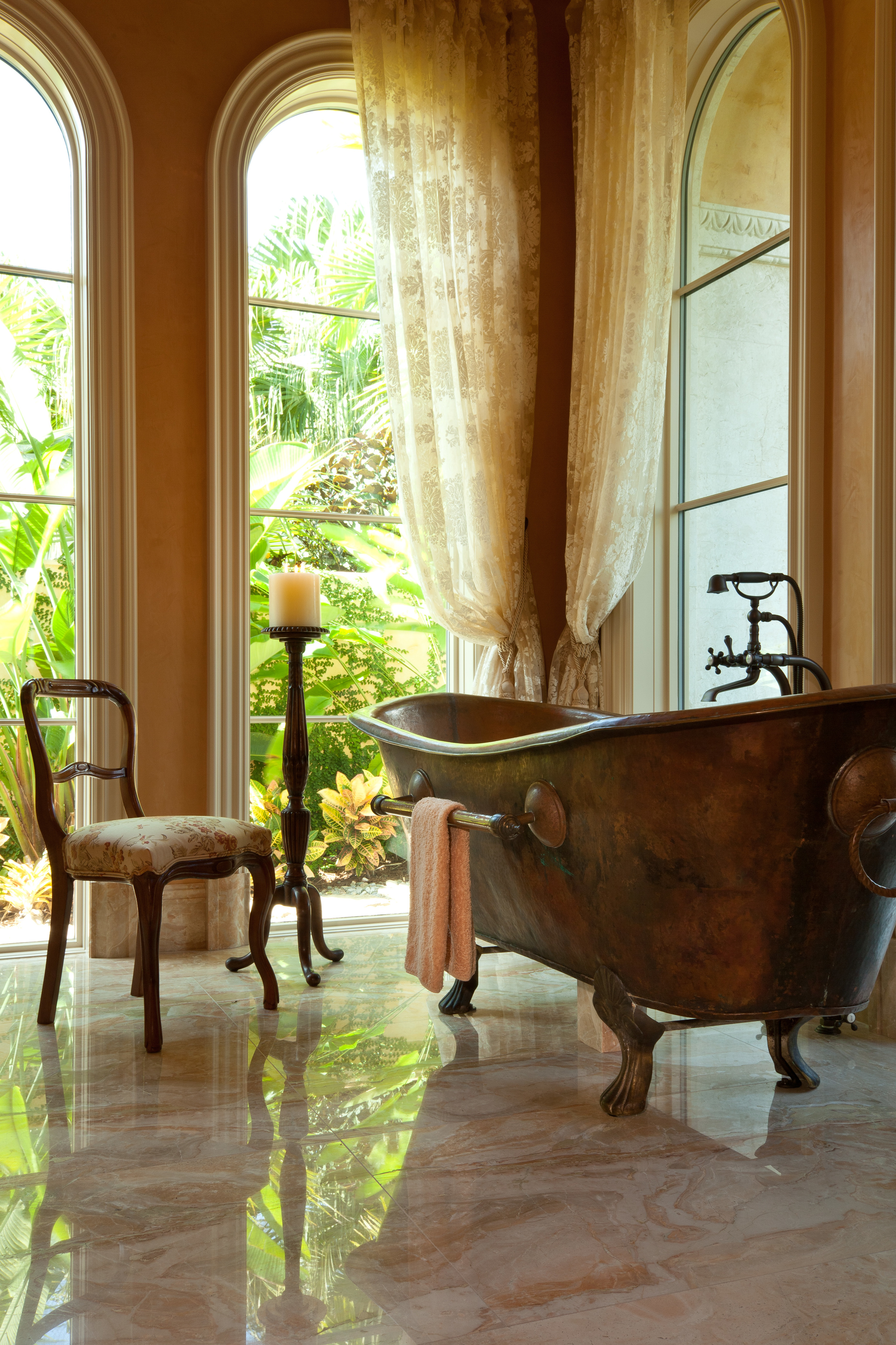 There is a view to a secluded courtyard from the antique French copper tub in the master bath of a remarkable Florida home, which is characterized by superbly detailed millwork.
