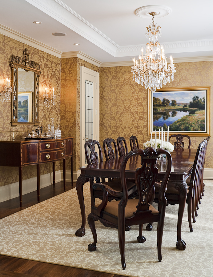 We created a superb setting for this family's art collection and their existing Chippendale furnishings, which we complemented with an antique chandelier and antique mirror. The gold on gold wallcovering and carpet create a soft and graceful backdrop, with a warmth that is especially welcoming at night.
