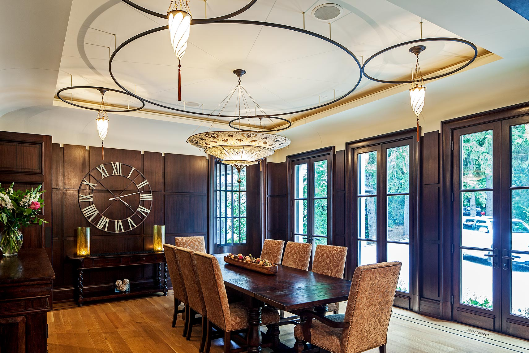 The formal dining room's simple elegance is deceptive; founded as it is on layer upon layer of unusual details. Matching a wall alcove opposite, the D-shaped window on the end wall comprises thermopane lights in an iron frame. The reveal line around the recessed centre panel emphasizes the gentle curve of the sculptural transition to the oval ceiling. In the mahogany wall panels, recessed fixtures in the shortened reveals accentuate the resulting crenellation, while washing the ceiling curve with light. Above, floating iron rings frame the Fortuny silk pendant lamps.