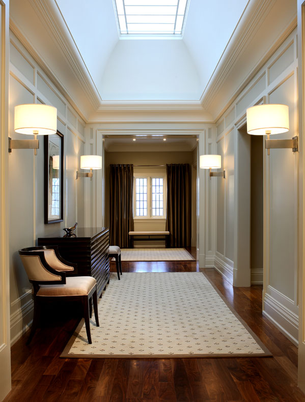 The long upper hall's rhythmic pattern of doorways, arches and sconces is bathed in light from one custom polished nickel high lens. To achieve symmetry, the three windows were draped to look like two.