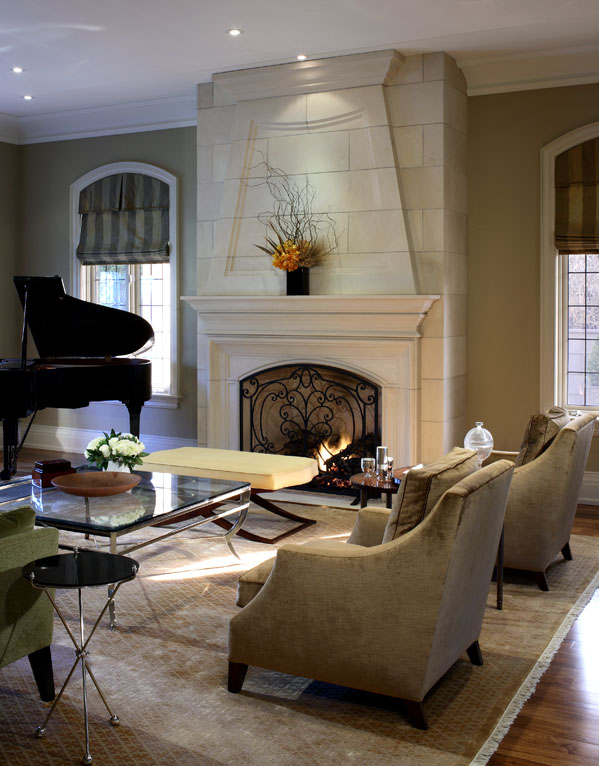 After conceiving all the interior volumes and spaces, we used a variety of motifs, textures and patterns so that each room has its own mood, yet a common richness unites the home. Here, the inviting living room combines contemporary furnishings with a stunning, traditional limestone fireplace.