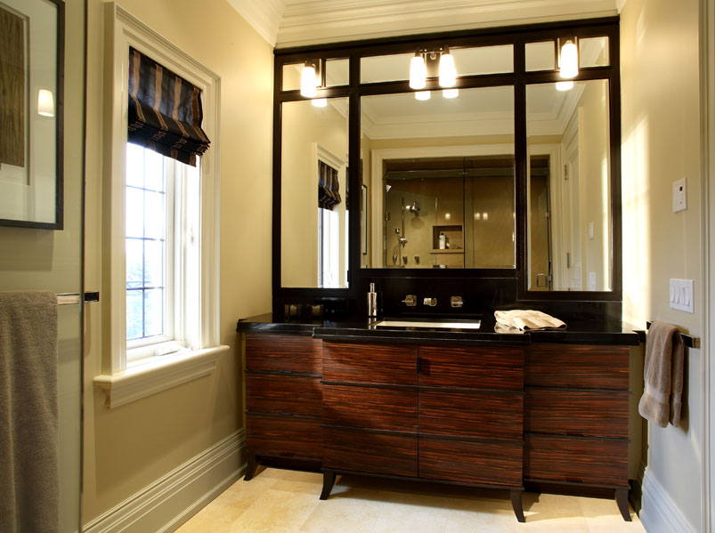 Combining sophisticated masculinity with classical detailing, his bath features rich, dark woods in a custom furniture-like vanity and a crisp window blind in chocolate and taupe.