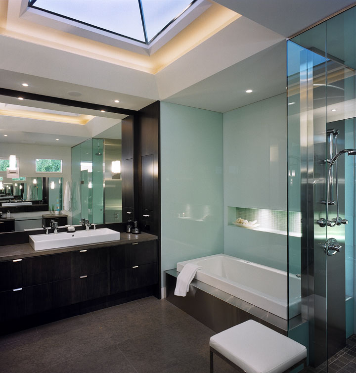 Their master bath seems infinitely spacious with its many reflective surfaces and sleek fittings. The stainless steel water column between the tub and steam shower visually expands the space as do the floor-to-ceiling enclosures. The custom skylight enclosure with dropped lens adds interest and height.