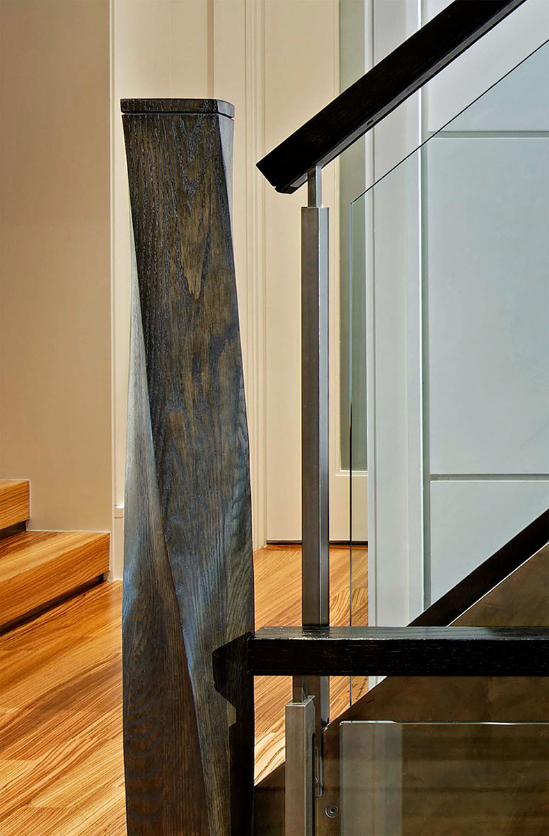 Careful detailing top to bottom make the central vertical circulation at the spine of this home its most powerful design element. Here, the gracefully sculpted wooden newel post emphasizes the change from the base step's curves to the straight lines of the stair rail.
