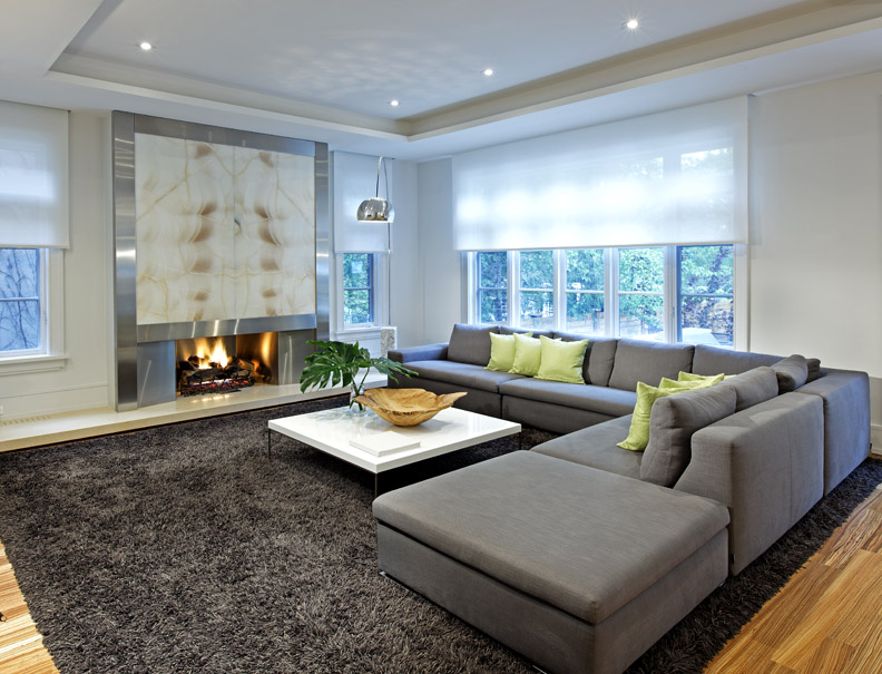 The generous and comfortable family room is awash with natural light in daytime and bathed in the glow of the backlit onyx fireplace later when the blinds fully drop from their concealed housing.