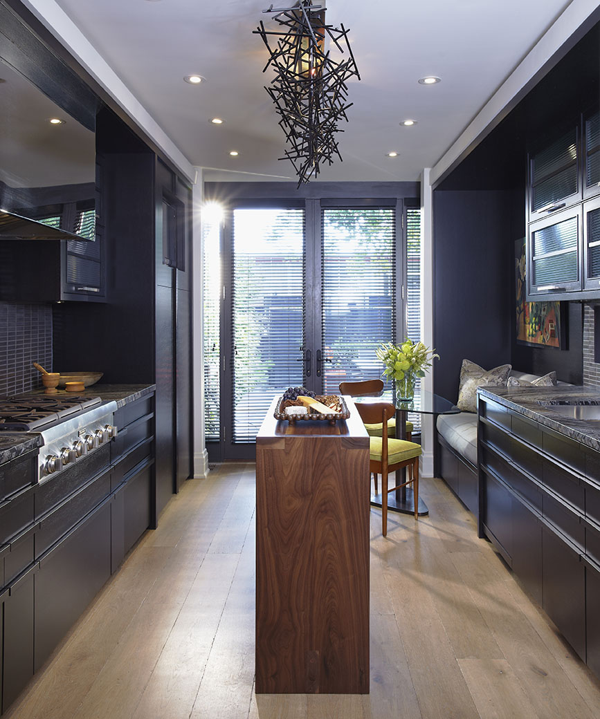 """Working with a long and narrow space, a galley-style kitchen was created with integrated, hidden appliances. A 16"""" wide custom designed island is the perfect plating size for 6 dinner guests. Upper cabinets flip up and out of the way for easy access while cooking. Lower pull-out cabinets have integrated handles for a streamlined look. The richness of the charcoal colour, combined with the oak floors, creates a warm cozy feel. Clean lines are complemented with a striking custom light fixture by Zac Ridgely."""