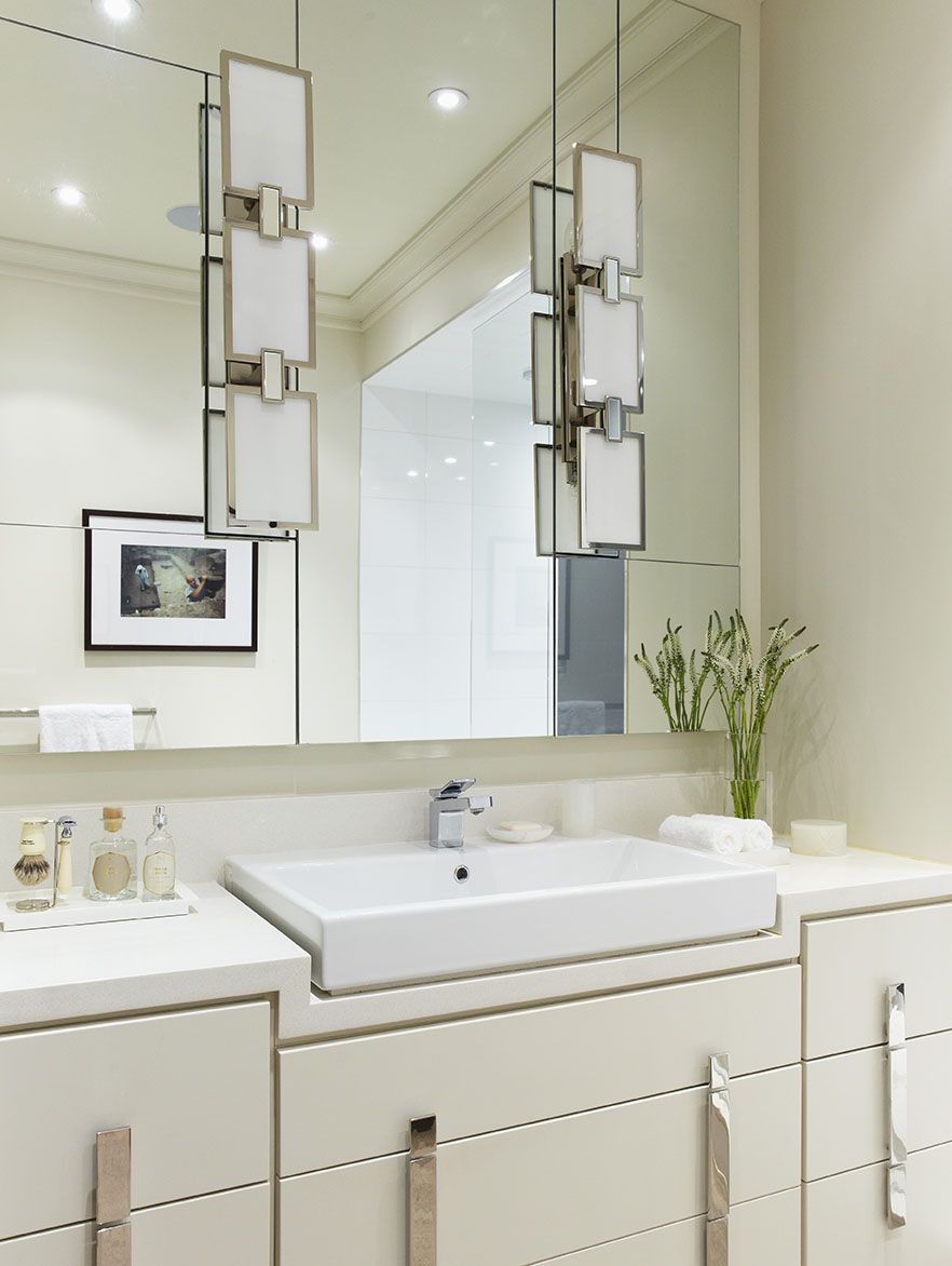 """Creating a clean and fresh space, the sink and vanity in this master bathroom nestle into the Ceasarstone top. The mirrored medicine cabinets are configured around the lights and open from a lip at the bottom, segmented in a """"Mondrian"""" pattern to conceal the joints. Each cabinet divisions the mirror and opens at a slightly different shape. The sconces are mounted directly onto the mirror, without sacrificing storage space. Custom cabinet pulls add to the clean and contemporary feel."""