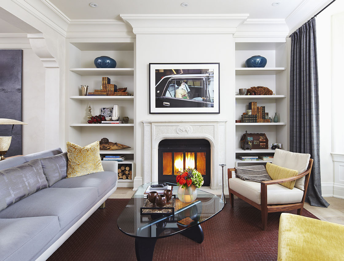 From the previous renovation, the only thing preserved was the original zero-clearance, wood burning fireplace. A custom designed mantle was hand-carved with solid stone and finished with a beaver motif. The openings in the cabinetry housing the firewood are made of durable Caesarstone, eliminating scuffing, while matching the painted finish of the surrounding cabinets. The custom designed sofa provides seating around an original Noguchi coffee table. Family heirlooms and treasured accessories add a personal touch.