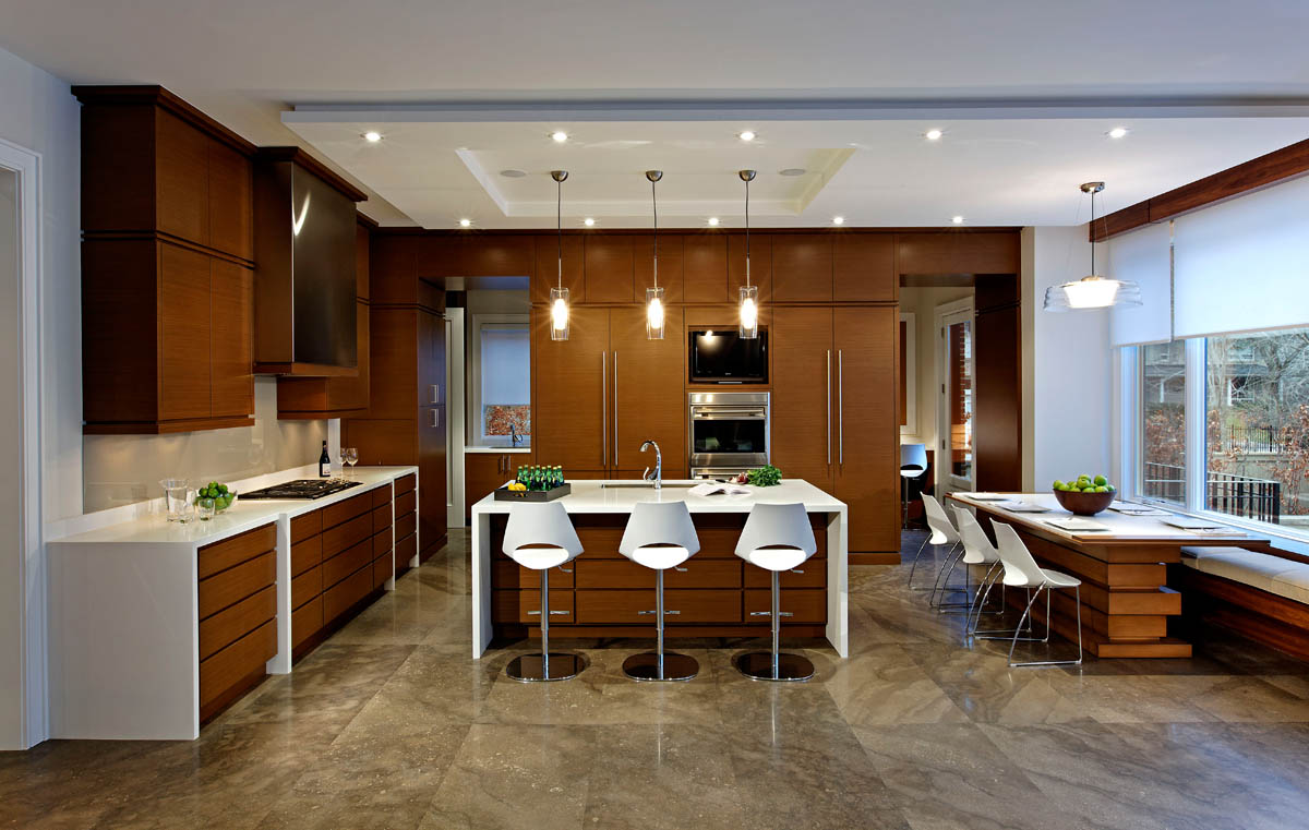 """In this pared down, yet welcoming space, the limestone flooring pattern is made even more prominent by the contrast with the simplicity of the kitchen cabinetry. The ceiling detail, """"stacked and wrapped"""" counter units and breakfast table reflect the layering and sculpting throughout the home."""