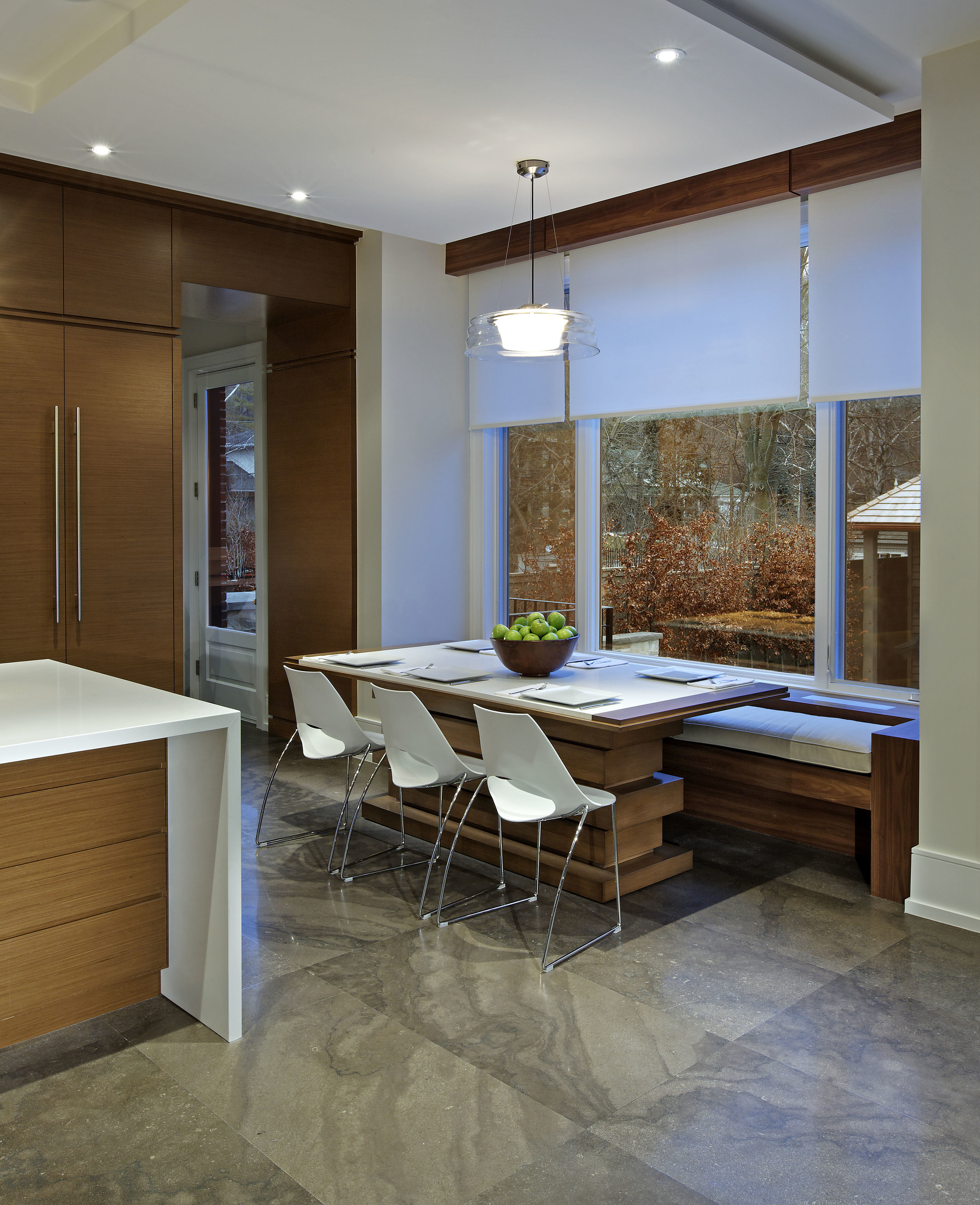 Within its austere modern context, this family home is filled with warm and inviting spaces such as this breakfast nook tucked into the kitchen window area.