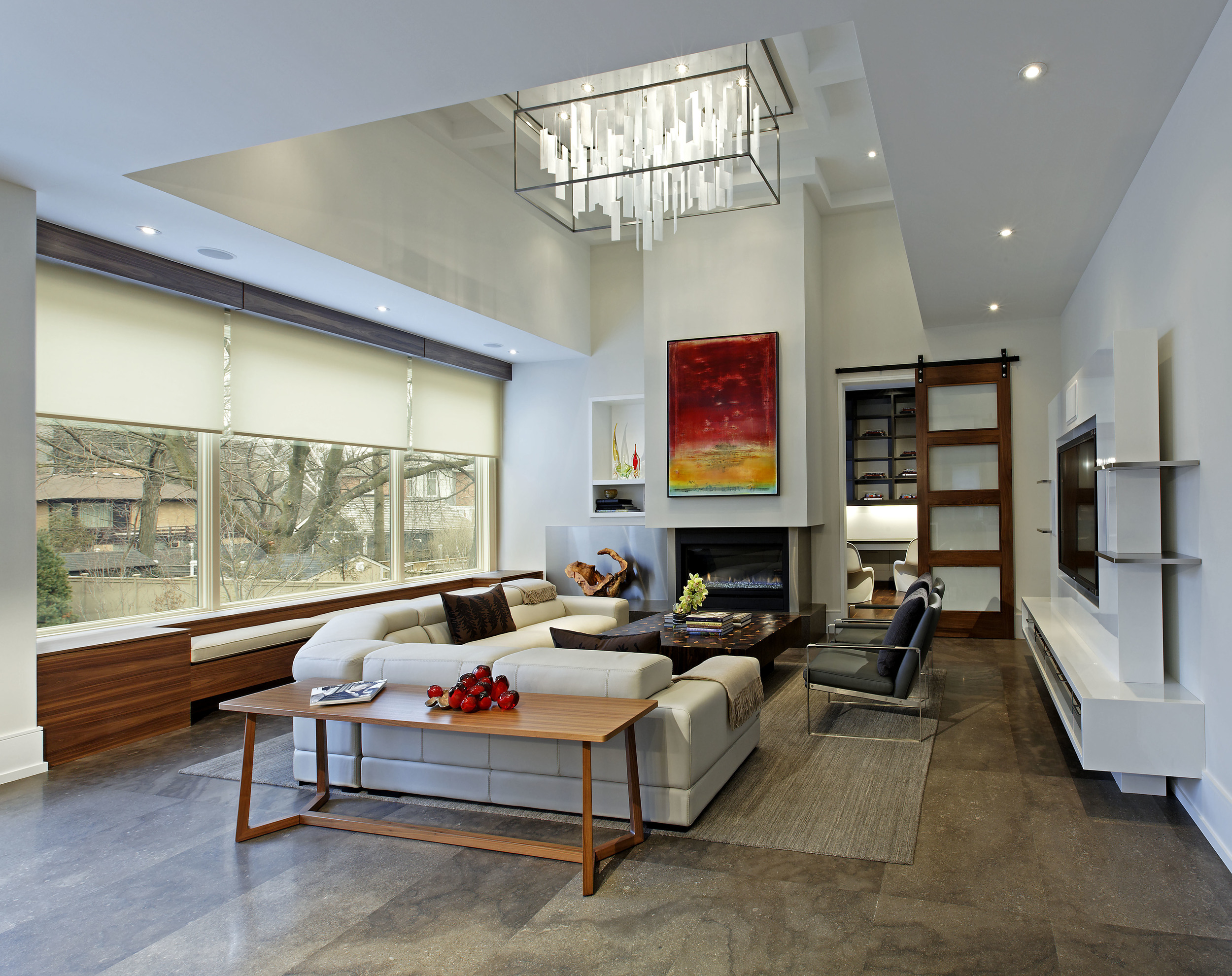 This room epitomizes the inviting, cozy, family-oriented environment created within a pared down, modern context. Its layering and sculpting includes seating and storage units tucked under the windows, below carefully planned bulkheads and a coffered ceiling and custom light fixture.
