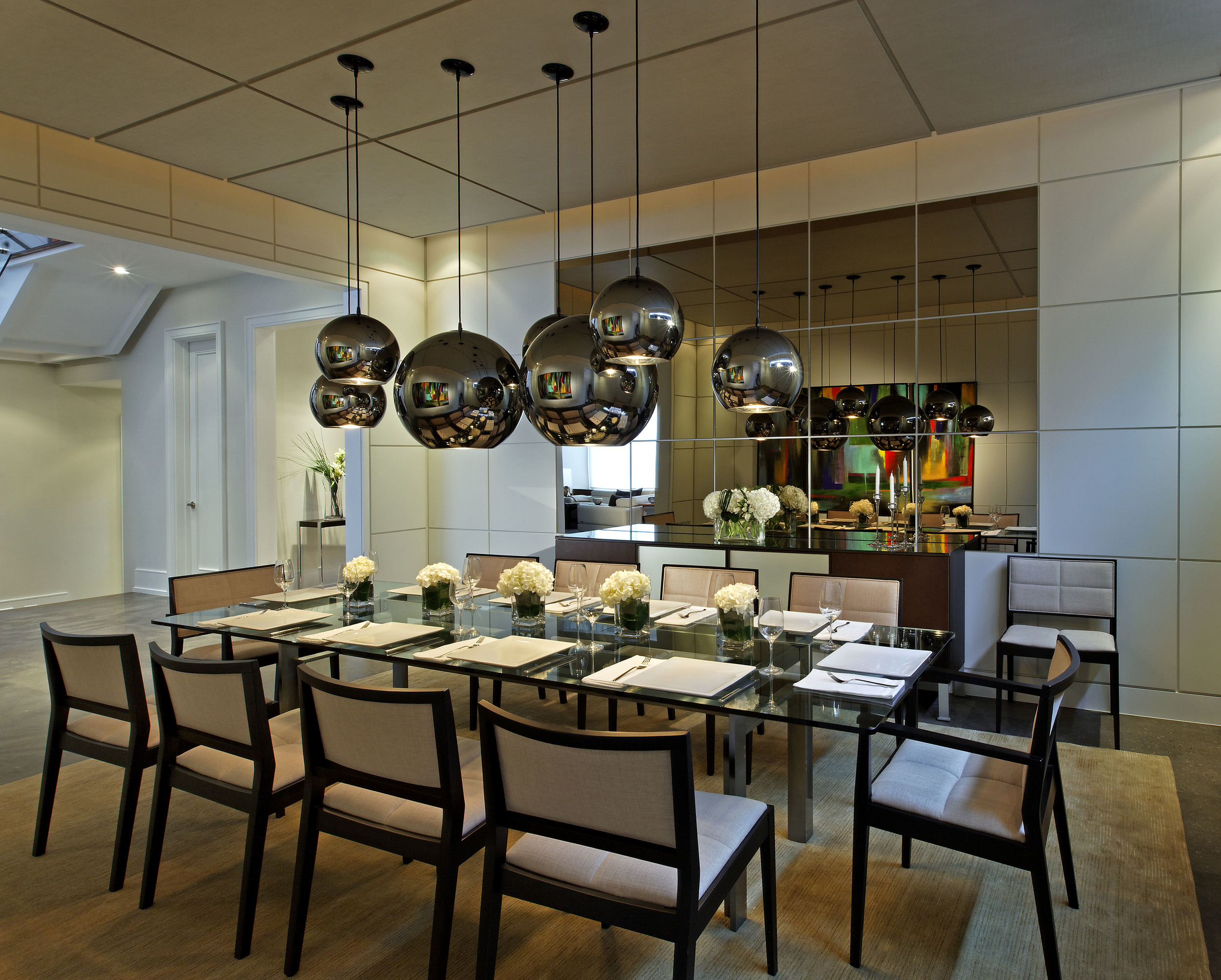 This long-awaited, custom-designed dream home balances the couple's love of pared down, austere, modern environments with their desire for an inviting, cozy, family-oriented environment. Bronzed mirror panels set into the dining room's painted panel walls with ½ inch reveals, reflect the furnishings, art and playful pendant lights. Those highly reflective fixtures themselves create infinite layers of colour and shape, in which is actually a very simply finished room.