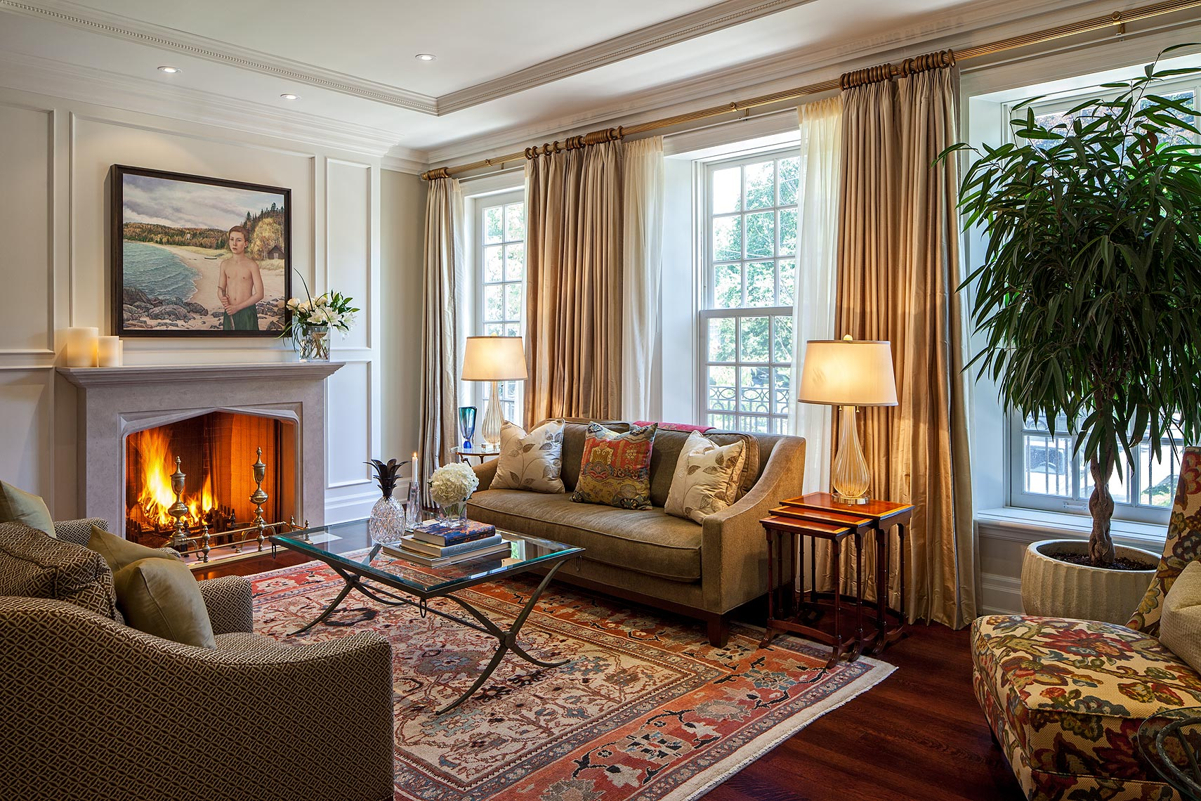 """This warm and gracious living room epitomizes the casual comfort that was created in a traditional home designed for a large and active family. Throughout it, the design and decoration incorporate a remarkable interplay of colour, pattern and texture, an important collection of Canadian art as well as antique and contemporary furnishings from around the world. Here, """"Boyhood"""" by Northern Ontario artist, Valerie Palmer is featured as well as an Sultanabad Persian carpet from the late 19th century. Toss cushions and an upholstered side chair reference the rich colours and pattern of the carpet."""