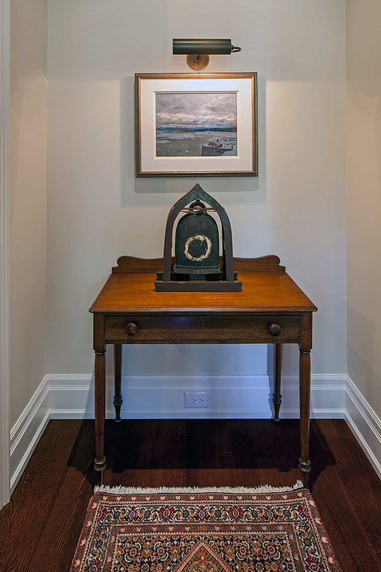 """Placing the owners' collectibles to best advantage was one of the great pleasures in designing this home. Here, in a small space just outside the study, an eclectic combination of pieces creates an arresting display. On a little antique Canadian table, a traditional bronze elephant bell from India sits below """"Winter, Beaupre"""", by Maurice Cullen, a historical Canadian artist from Montreal."""
