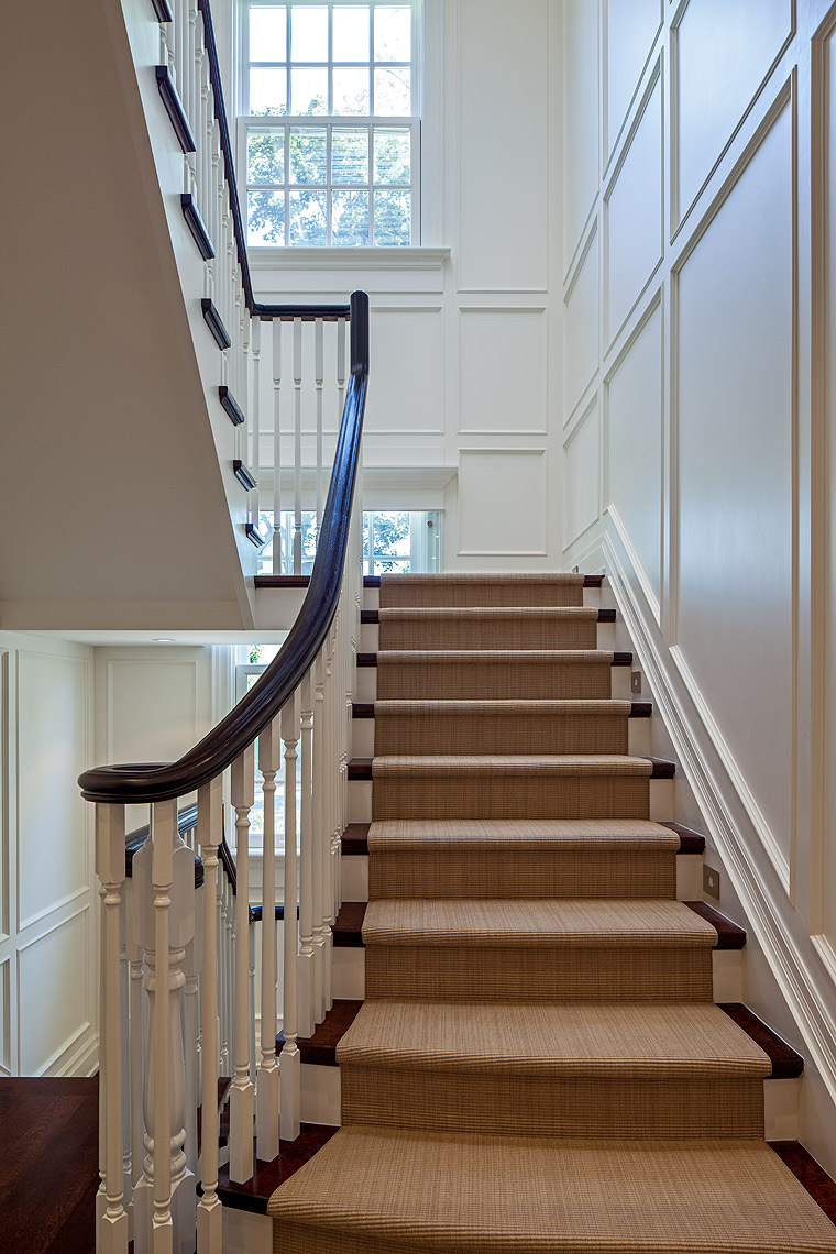 The exquisitely scaled paneling and stair details were carefully designed to reference the Georgian design of the exterior of this home and to create a graceful connection between the windows and landings. The simplicity of the flat-woven grass cloth carpet compliments this airy, light-filled space and is a practical choice in a home with eight pets.