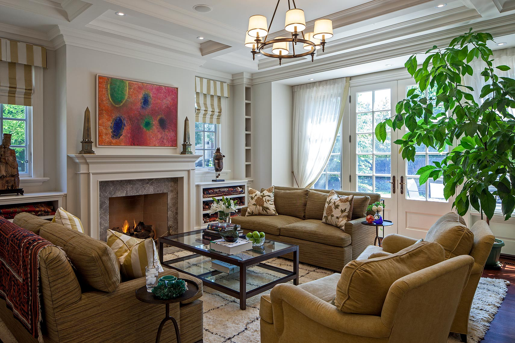 """Perfectly symmetrical, the complex wall and ceiling details are both elegant and functional. The marble fireplace centres a carefully planned storage wall that flanks the windows with small niches housing gemstone specimens collected by the owners, both geologists. The painting is """"Celestial Gathering"""" by historical Canadian artist Michael Forster. Below a historic sculpture and mask, large shelves provide storage for several antique carpets. The coffee table and seating were existing; new upholstery stands up to use by children and pets, as does the handmade Jan Kath carpet. The crewel work cushion covers reflect the owner's love of textiles."""