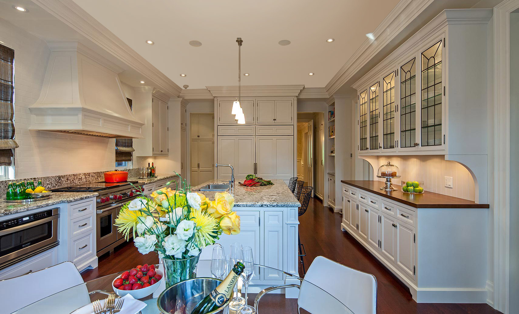 The carefully designed cabinetry includes a large unit designed to look like a freestanding hutch, with its furniture-like base detail, brackets, black-leaded glazing and wooden counter top.