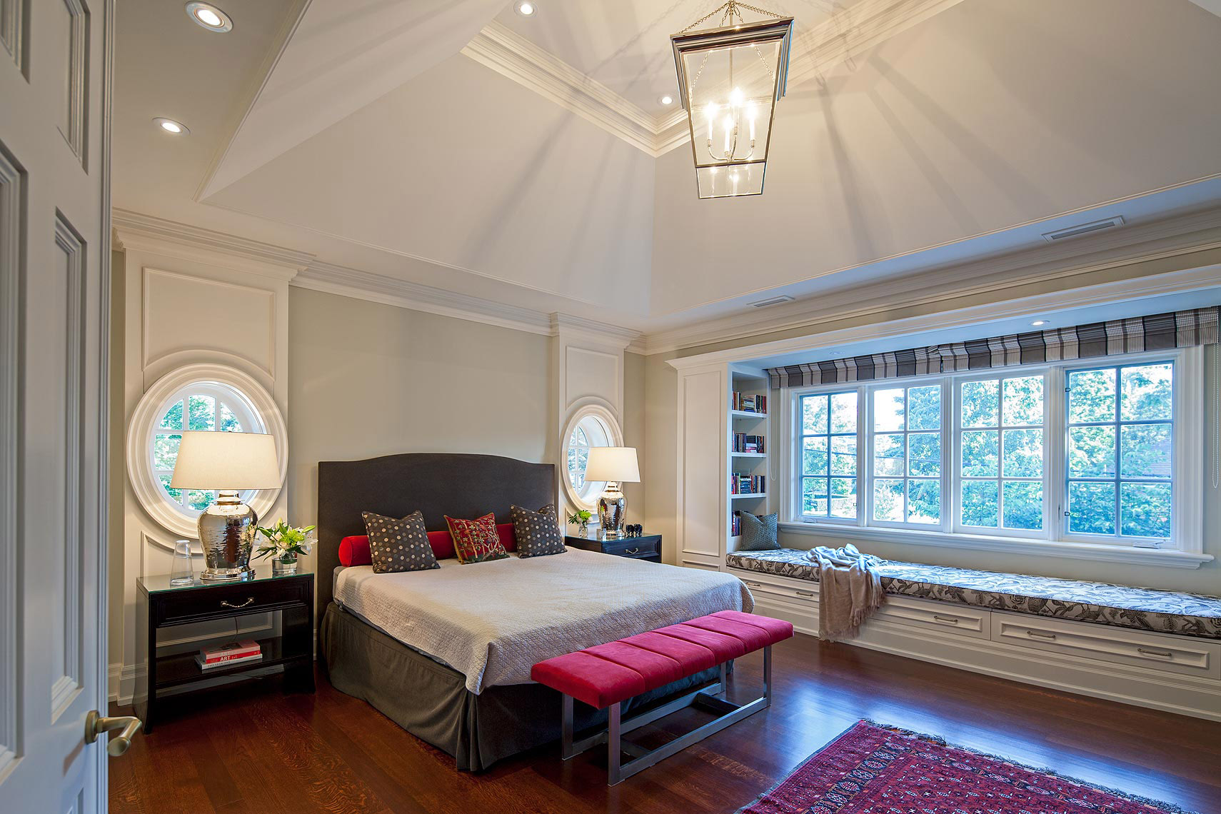 The upholstered headboard is perfectly framed by the panelled wall, which incorporates two oval windows above extra-wide cabinets. The window casings were designed to conceal pull down blinds for privacy. The adjacent wall was built out to incorporate storage and an 11 foot long daybed under the huge window. The serene colour scheme is accented with red elements such as the bench cushion and the throw pillows' large scale prints, which reference the antique fabrics and carpets found elsewhere in the home. Nickel finishes on the lamps and hardware add sparkle.