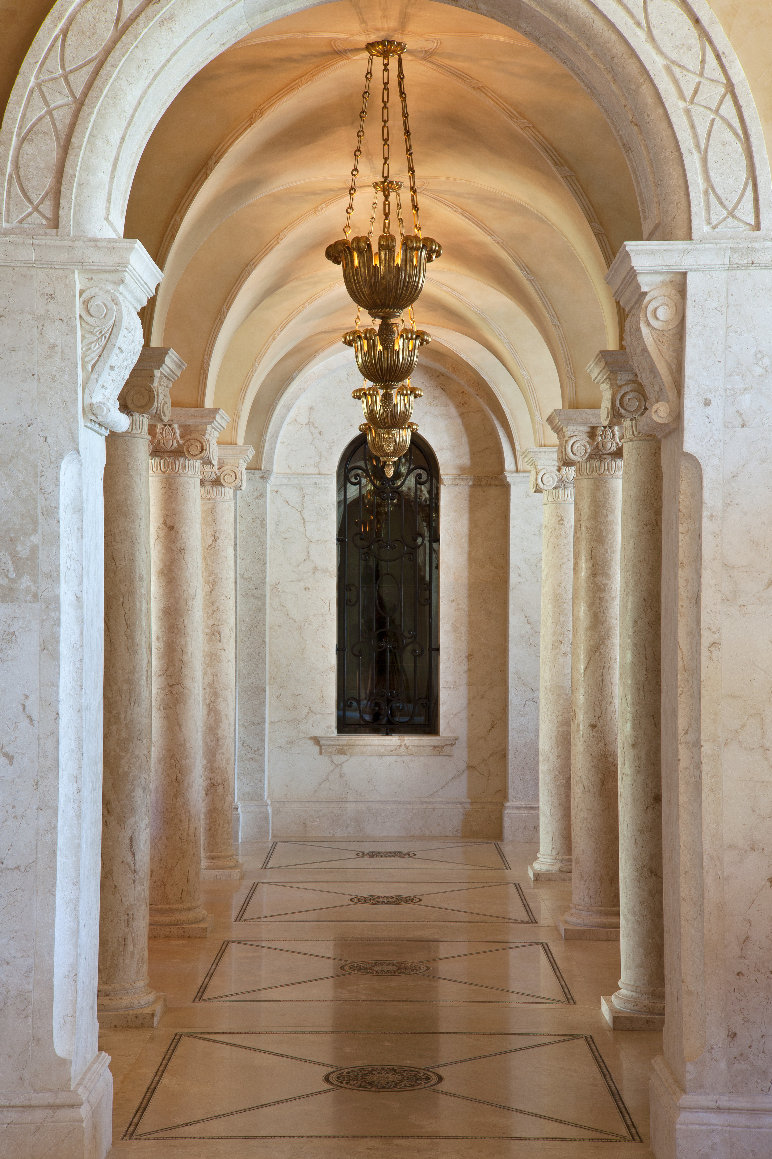 The vaulted corridor was designed to provide access to the great room on the west side of the house and culminates at the entrance to the wine cellar iron grille. The floor and ceiling were carefully planned out so that lanterns hang directly over the complex medallions laser etched into the limestone flooring.