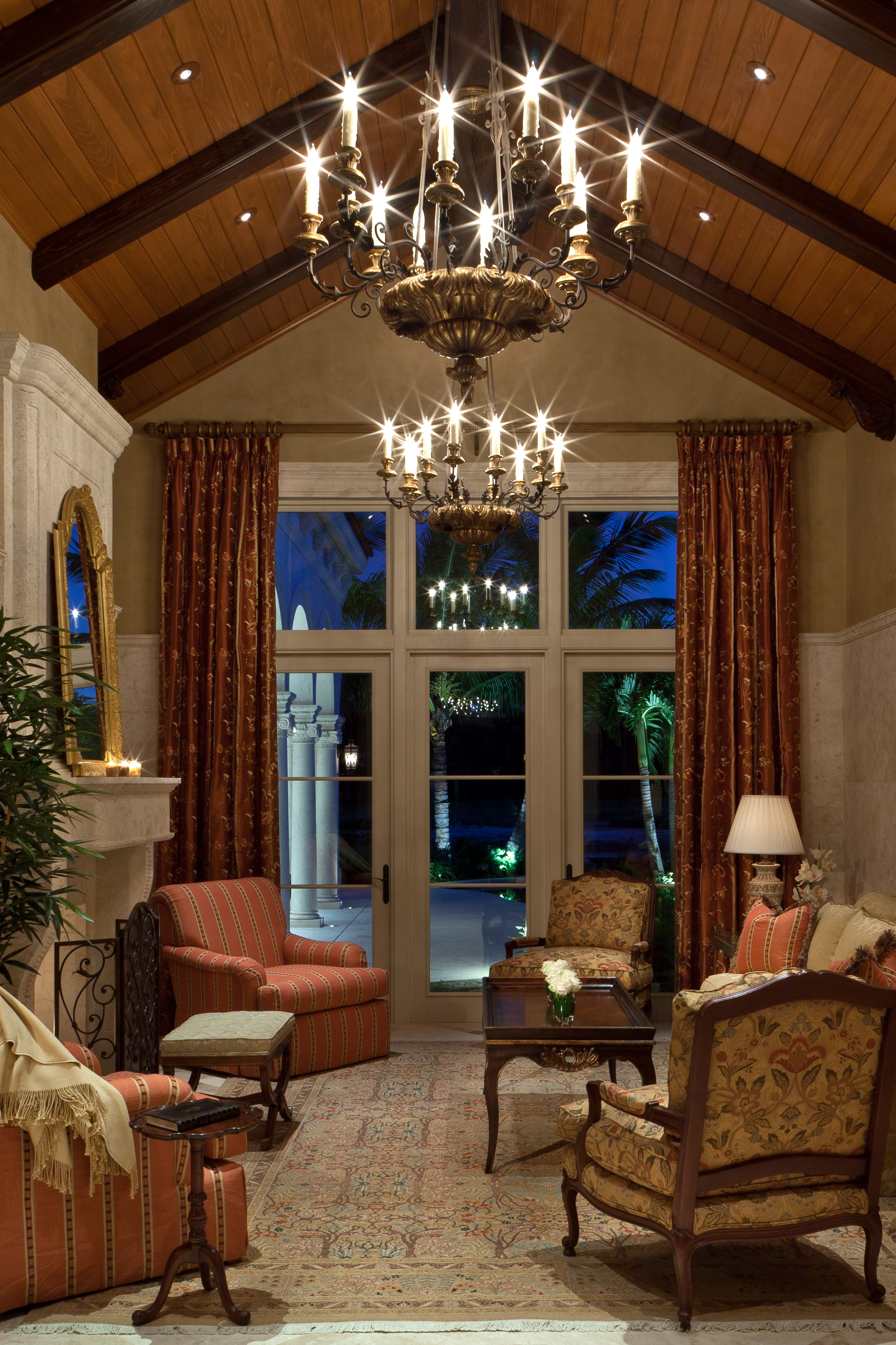 In this warm and welcoming living room, the stone paneled walls and superb custom designed, carved mantelpiece called for precise and innovative detailing, as did the ceiling structure of mahogany beams and cypress panels.