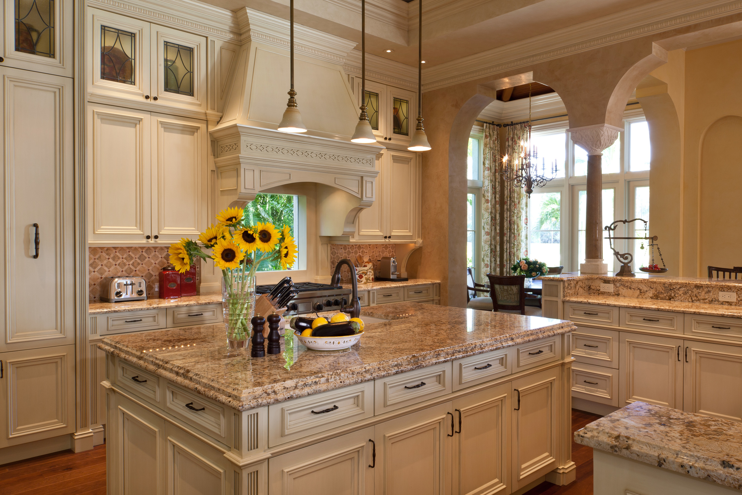 This 400 sq. ft. kitchen is a masterpiece of detailing and collaboration with the cabinet maker. Every inch of the cabinetry was custom designed for function and to integrate with the interior architectural elements. Like the large colonnades elsewhere, the small columns have a Moorish flavour. The proto-Grecian column capital reproduces one seen on the owners' trip to Turkey. Pale painted finishes and granite reflect the glorious light that floods this Canadian couple's Florida winter home.
