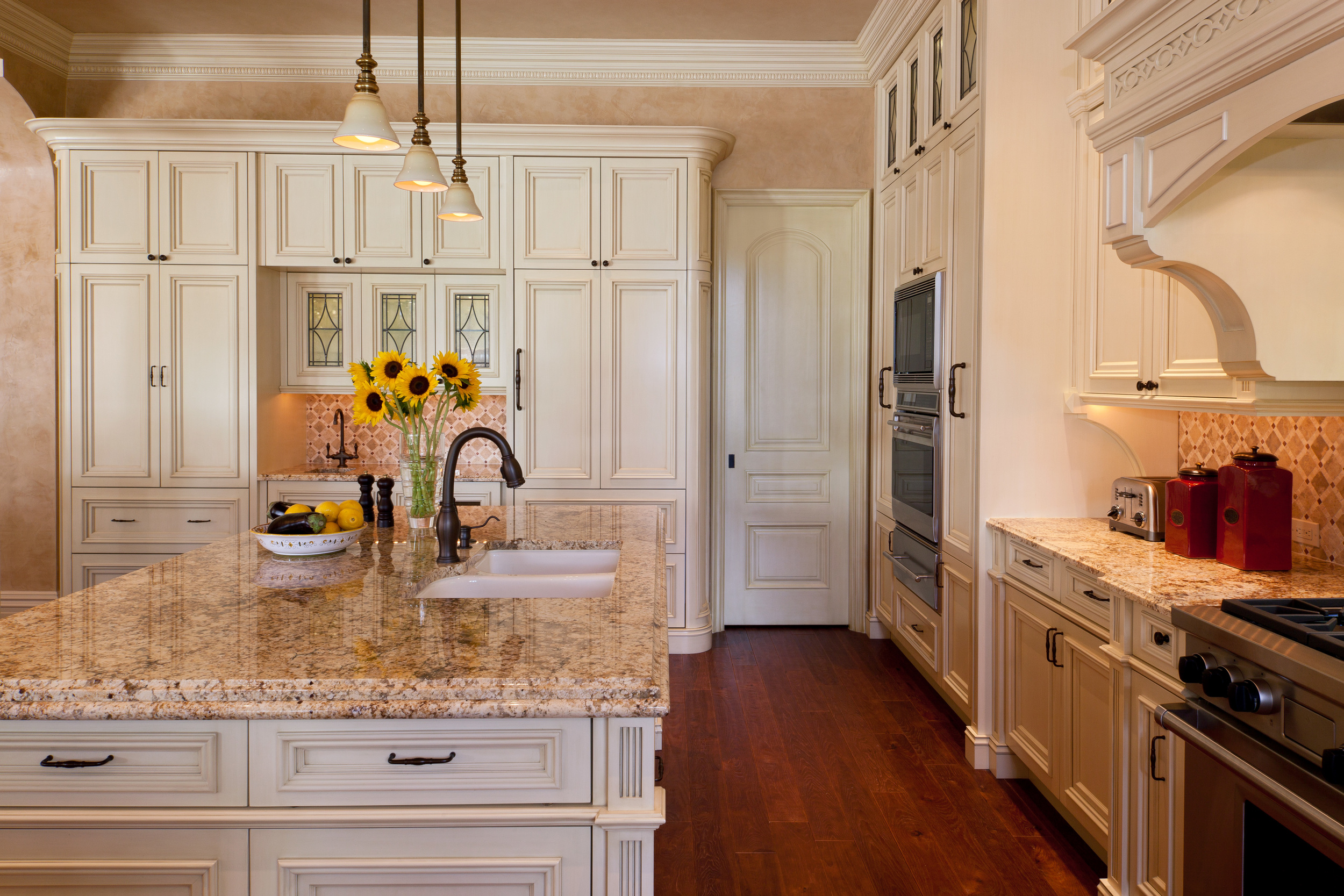Nestled into the pantry wall, the large storage and bar unit sits perfectly below the coffered ceiling. They myriad of special details in this kitchen cabinetry and architectural millwork marry flawlessly.