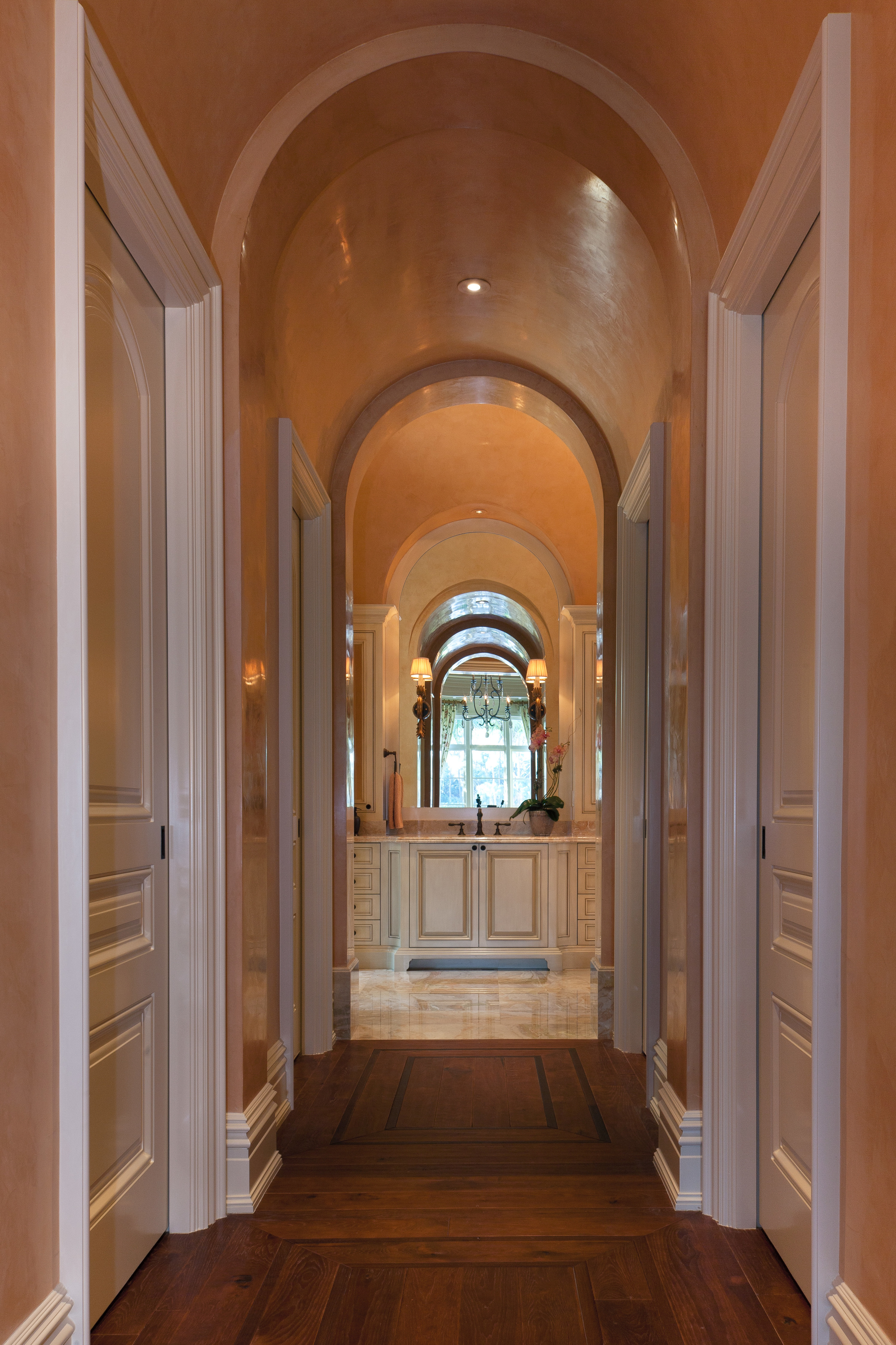 Seen from the master bedroom doorway, this short corridor leads to the master bath and incorporates openings to dressing rooms, toilet area and shower room on either side. The delicate archway and fine plaster finish reflect the other finishes in the home; the hickory flooring is used throughout, in diverse patterns. The gracefully detailed vanity cabinetry at the end of the corridor rises above breccia oniciata marble slab flooring.