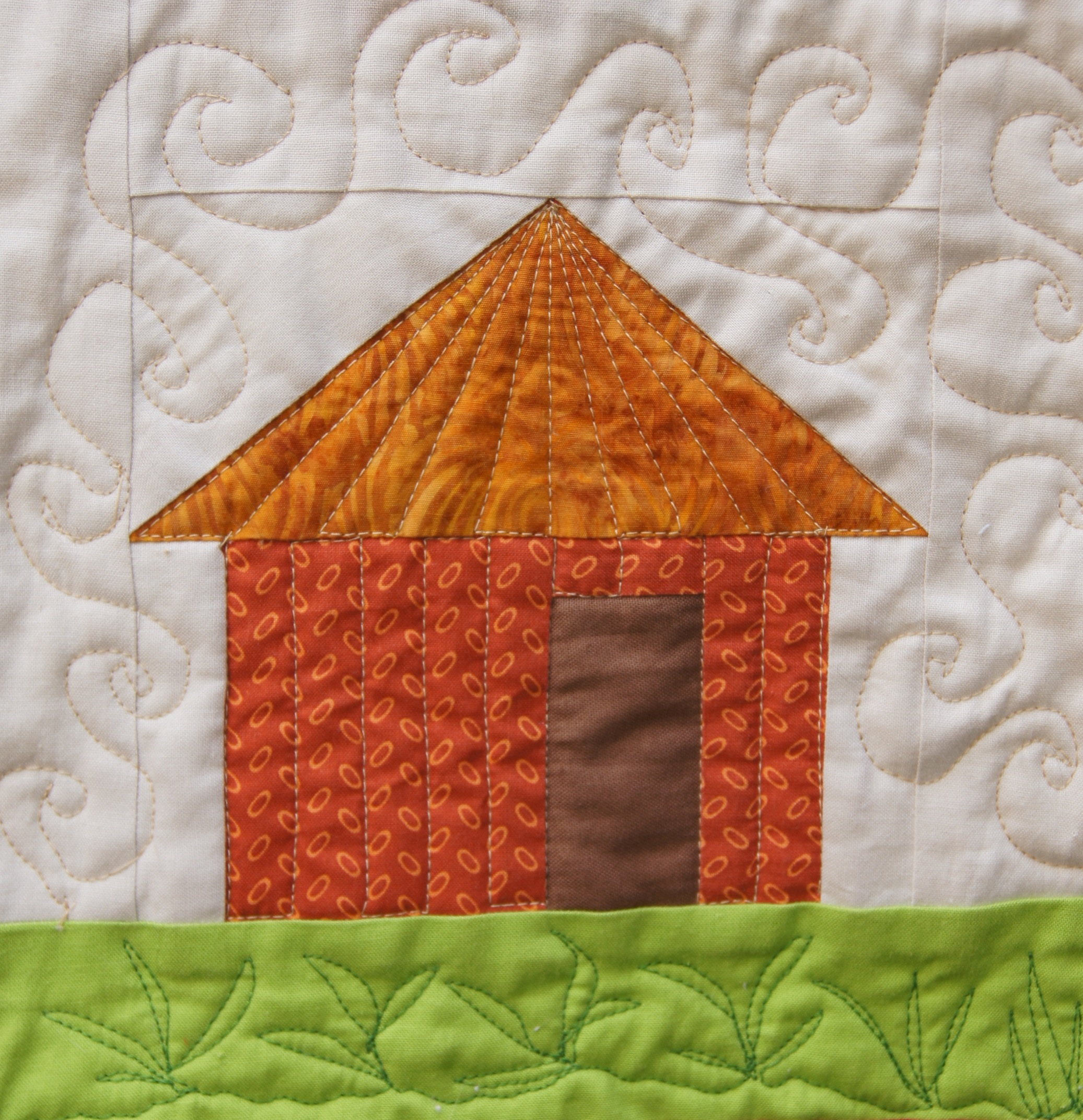 Radiating quilting done with walking foot on the hut roof,  Free motion quilting used to create grasses and heat swirls.