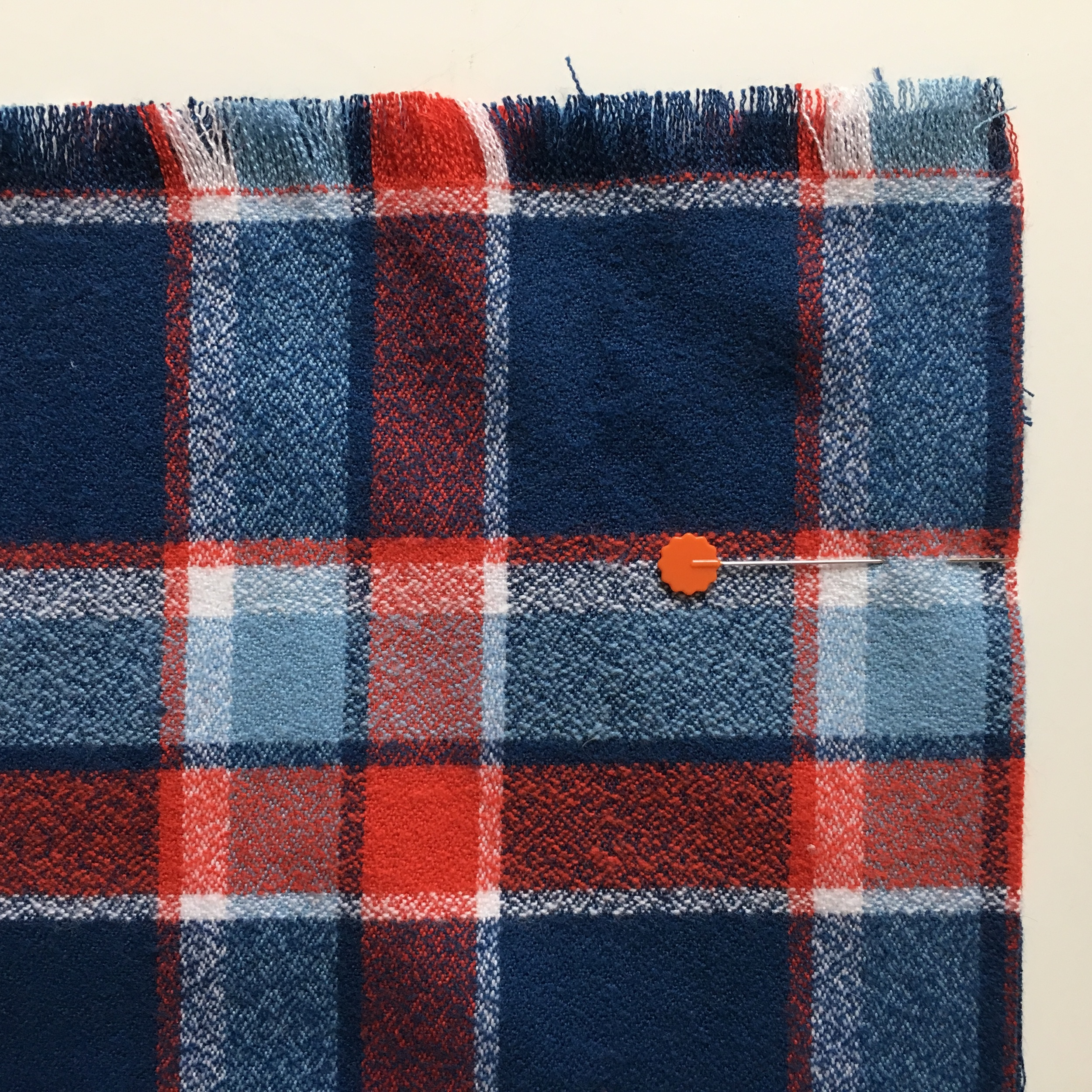 The scarf is folded in half the long way and pinned on the raw edge, matching the plaid carefully