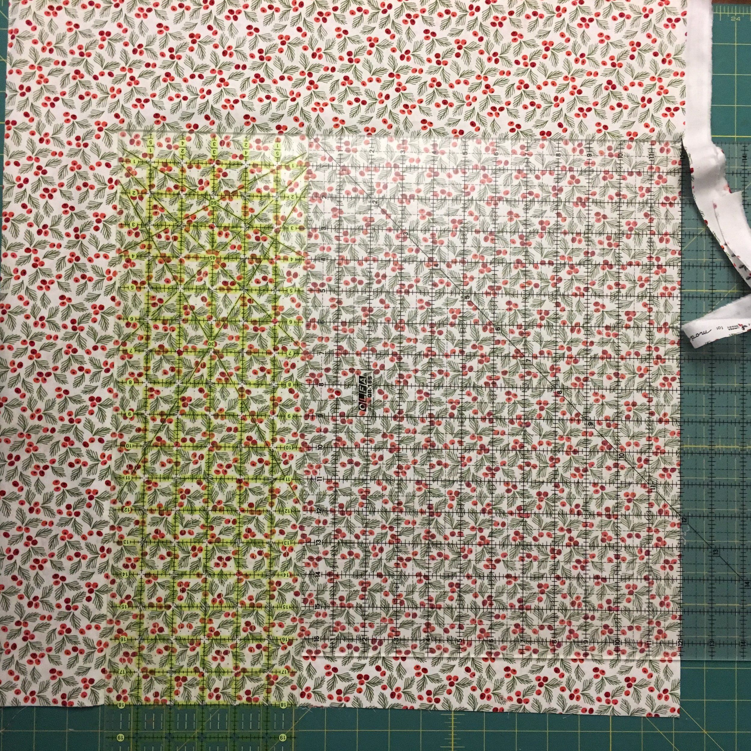 24 inch ruler is on the left, with the quilting square on the right. The fabric cut will be 18 inches long and 18 inches wide. Note the fabric at the lower right edge that isn't covered by the shorter square ruler. That's fine because no cut is needed there.