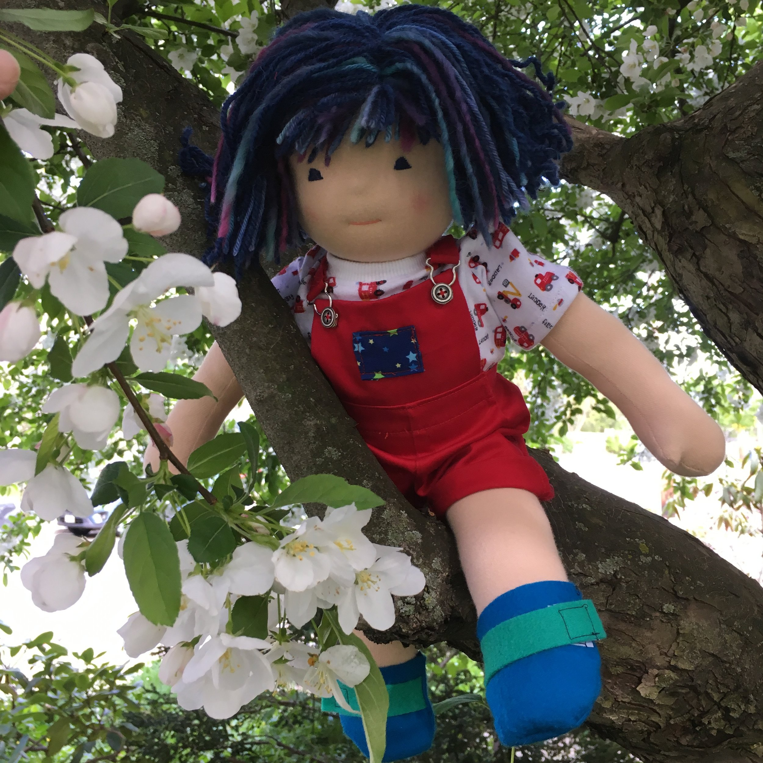 Douglas in the crab apple tree wearing the red overall shorts and firefighter T shirt I made for him