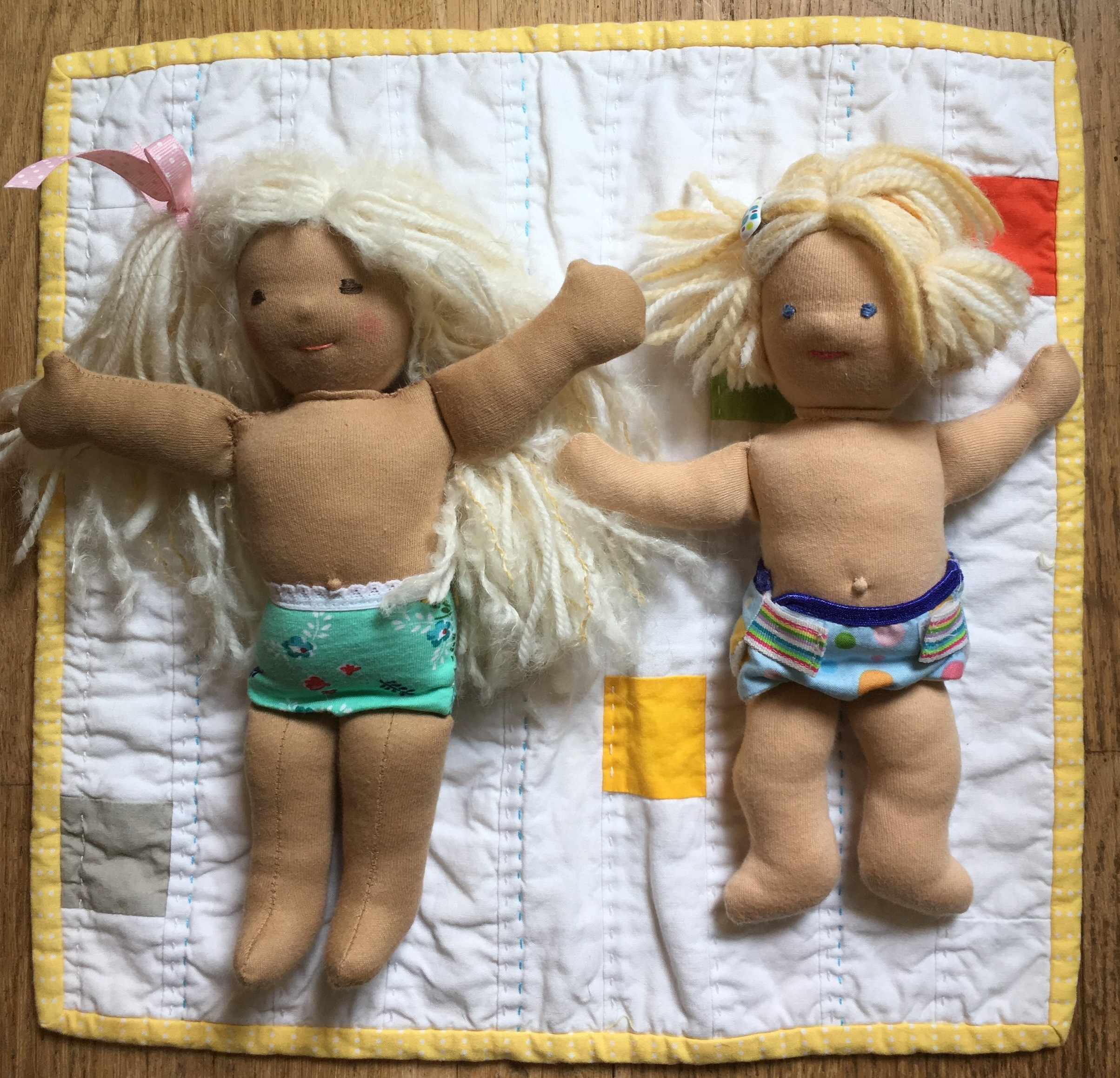 Little girl on the left, baby on the right. Phoebe has dark tan skin and Lucy's is skin is sunkissed