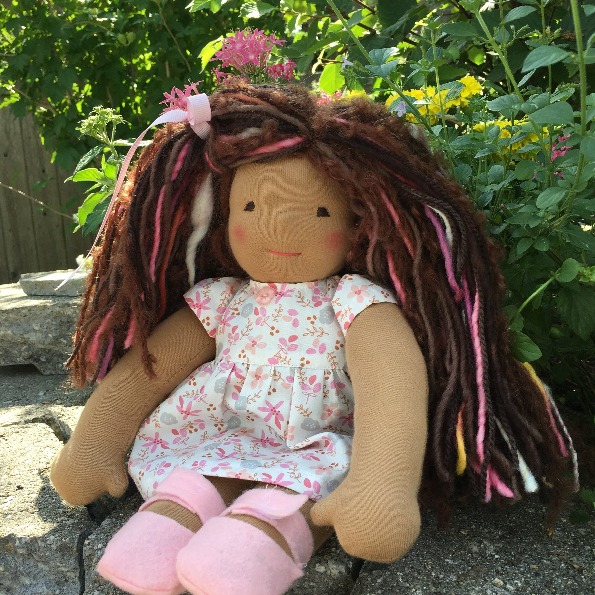 13 inch Waldorf type doll with dark tan skin and a variety of yarns in her hair